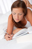 Young woman writing notes and lying on bed Royalty Free Stock Photography