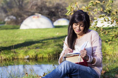 Young woman writing and reading a book in an autumn park. Beautiful woman writing and reading a book in an autumn park stock image