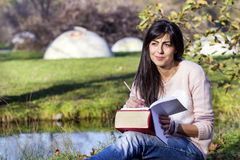 Young woman writing and reading a book in an autumn park. Beautiful woman writing and reading a book in an autumn park royalty free stock photography
