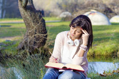 Young woman writing and reading a book in an autumn park Stock Images