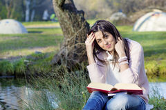 Young woman writing and reading a book in an autumn park Stock Photos