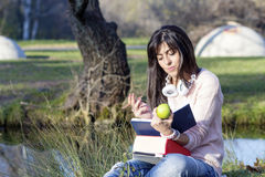 Young woman writing and reading a book in an autumn park Royalty Free Stock Image