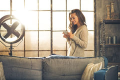Young woman writing sms in loft apartment Royalty Free Stock Photography