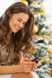Young woman writing sms near christmas tree Royalty Free Stock Images