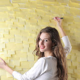 Young woman writing on some post-it Stock Image