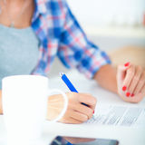 Young woman writing something in her note pad Stock Images