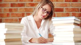 Young woman writing something by pen stock footage
