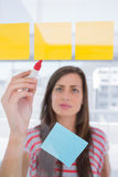 Young woman writing on sticky note Stock Image