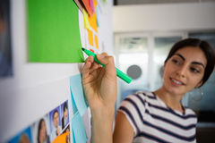 Young woman writing on sticky note at office. Businesswoman writing on sticky note at creative office Stock Photos