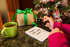 Young woman writing text - Happy new 2018 year. With christmas tree and presents on background Royalty Free Stock Photography