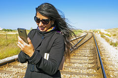 Young woman is writing a text message at a railroad tr Royalty Free Stock Image