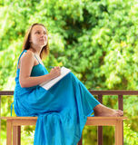 Young woman writing to notebook. Outdoor portrait Stock Photography