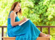 Young woman writing to notebook Royalty Free Stock Photos