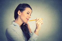 Young woman writing on a wall. Side profile young woman writing on a wall with pencil royalty free stock photography