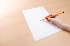 Young woman writing on a white sheet of peper Royalty Free Stock Photography