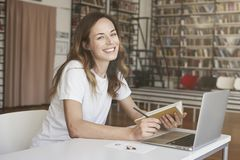 Young woman writing, working on laptop at sunny co-working office or library, bookshelf behind. Business Woman smiling. White t-shirt stock images