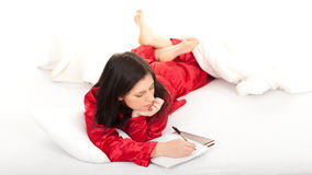 Young woman writting on clipboard in white bedding Stock Photo