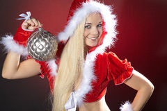 Young woman with xmas ball. Young woman with Christmas hat and xmas ball royalty free stock image