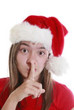 Young woman with xmas hat signalling silence Royalty Free Stock Photo