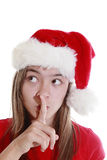 Young woman with xmas hat signalling silence Royalty Free Stock Photos
