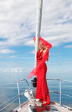 Young woman on the yacht. Picture of pretty young woman in red dress posing on the bow yacht Stock Photos