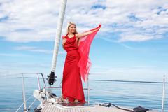 Young woman on the yacht. Picture of pretty young woman in red dress posing on the bow yacht Royalty Free Stock Images