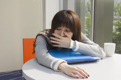 Young woman yawing in office Royalty Free Stock Images