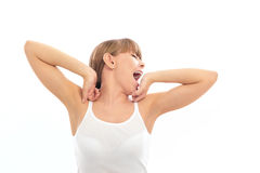 Young Woman Yawning. Beautiful young woman stretches her arms as she yawns to the side. Horizontal shot royalty free stock photo