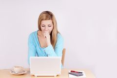 Young woman yawning in front of computer Stock Photos