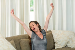 Young woman yawning and stretching her hands Stock Photos