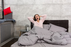 Young woman yawning and stretching while sitting in the bed and Royalty Free Stock Image