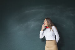 Young woman yelling in front of blackboard royalty free stock photography