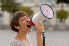 Young woman yelling into a megaphone or bullhorn. As she stands outside airing her grievances while participating in a protest Royalty Free Stock Image