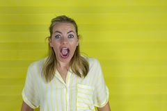 Young woman on a yellow background with surprise expression and excited face royalty free stock photography
