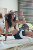 A young woman in a yellow bathing suit and a straw hat is sitting on a bed in a hotel room stock image