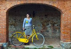 Young woman with yellow bike. Young woman in blue with old yellow bike stock photos