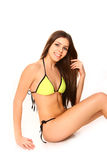 Young woman in a yellow bikini sitting on white background Royalty Free Stock Photos