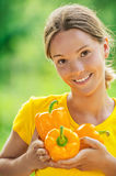 Young woman in yellow blouse with bell pepper Stock Images