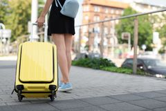 Young woman with yellow carry on suitcase Royalty Free Stock Photos