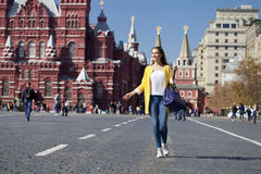 Young woman in yellow coat walks on the Red Square in Moscow Stock Images