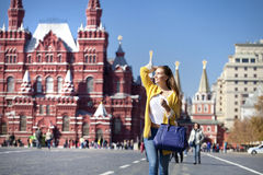 Young woman in yellow coat walks on the Red Square in Moscow Royalty Free Stock Photography