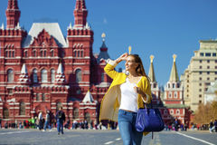 Young woman in yellow coat walks on the Red Square in Moscow. Young happy woman in yellow coat walks on the Red Square in Moscow royalty free stock photos
