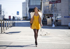 Young woman in yellow dress crossing the road outside Stock Photo