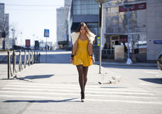 Young woman in yellow dress crossing the road outside Stock Image