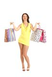 A young woman in a yellow dress holding bags Stock Images