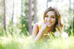 Young woman in yellow dress lying on grass Stock Photos