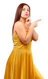 Young woman in yellow dress point finger showing something to si Royalty Free Stock Photography