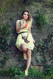 Young woman in yellow dress posing against old wall Stock Photo