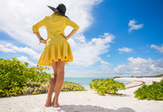 Young woman in yellow dress standing on the beach Stock Photography