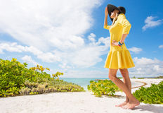 Young woman in yellow dress standing on the beach Stock Photo